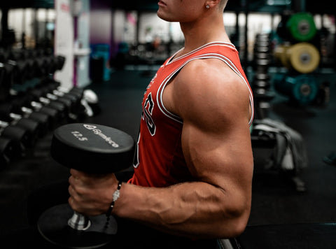 Bodybuiler in an orange jersey top carrying a dumbbell