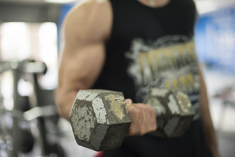 Muscled man working out with a dumbbell
