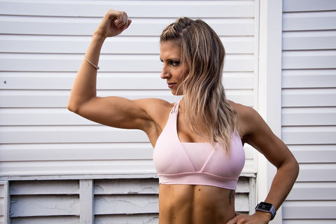 Woman flexing her arm in a pink sports bra