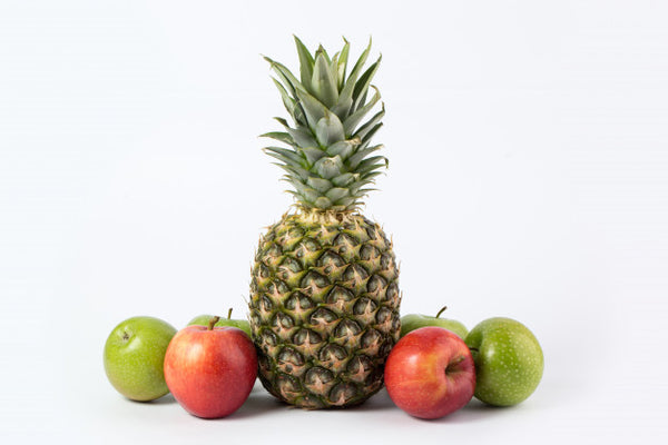 One Pineapple and four apples on a white background.