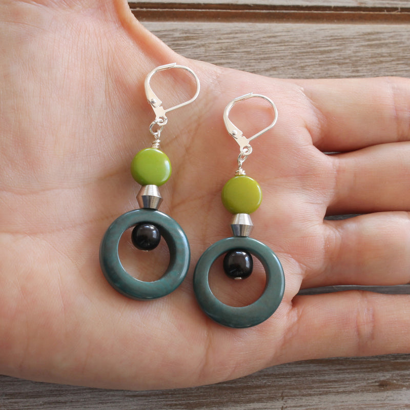 "These original tagua earrings have a real bohemian feel formed by a ring with a center hang and a delicate silver color piece coupled with another small round tagua piece on top . The silver metal look goes with everything and are the perfect size for gift giving!  Tagua is organic, sustainable and lightweight making it very comfortable to wear.  Rhodium plated nickel free jump rings Approximately 2.15"" long from end-to-end Tagua is Fair trade from Ecuador Handmade in Canada"