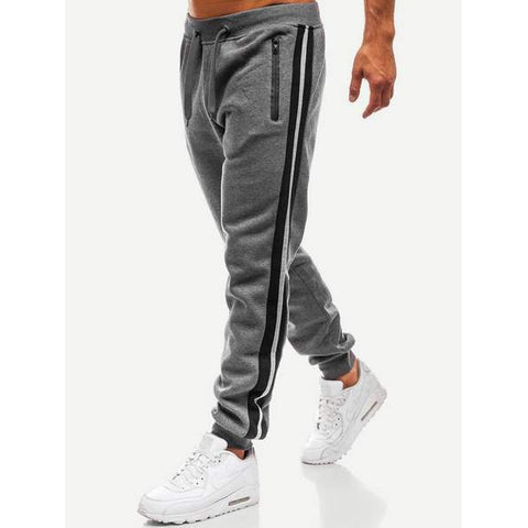 Sideview of grey sweatpants showing the stripes