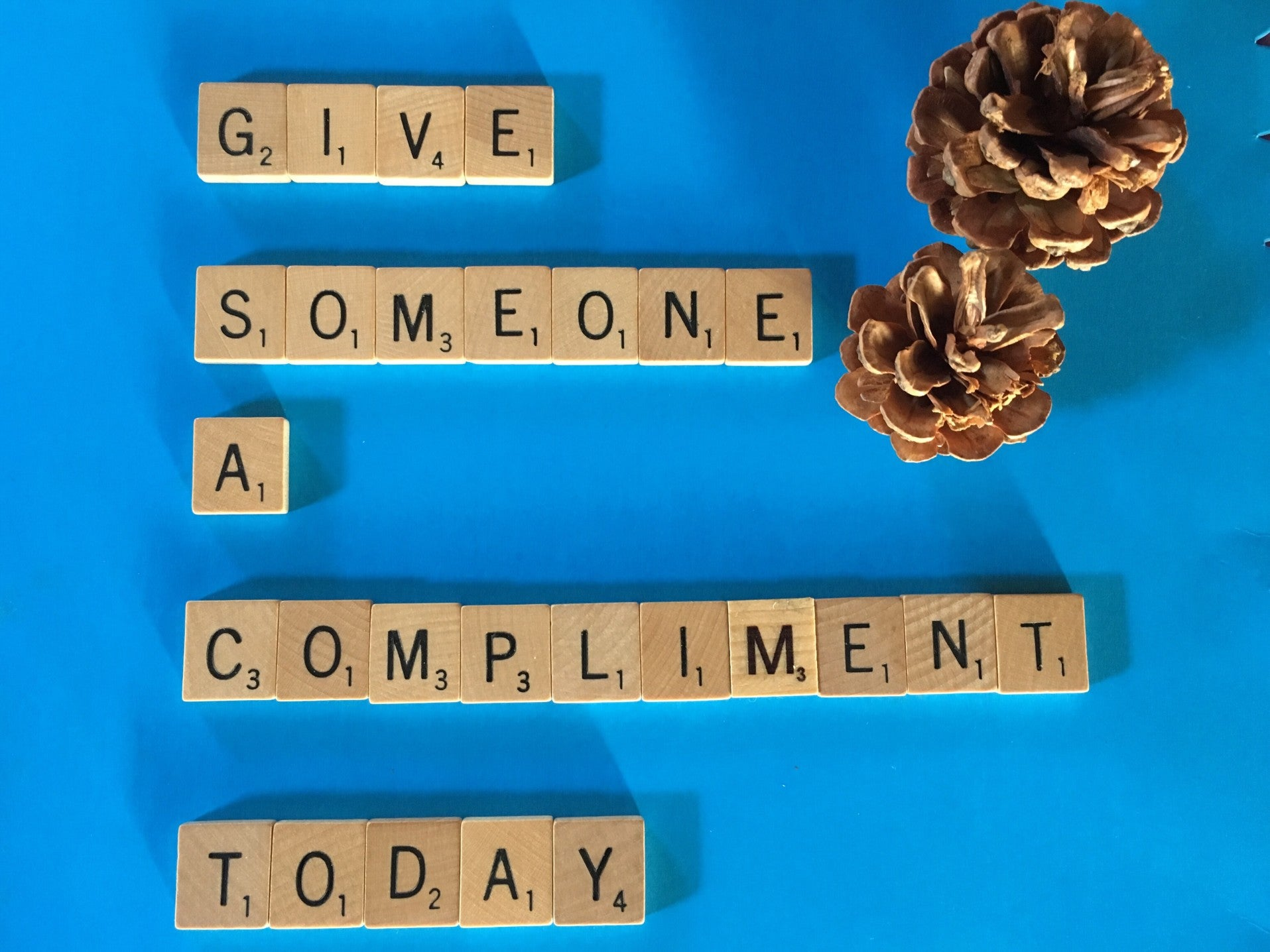 Image of scrabble tiles spelling out the phrase Give Someone a Compliment Today
