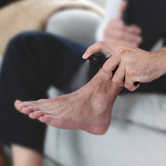 Man Spraying Foot Duster On His Feet