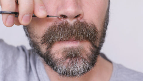 Man Cutting His Nose Hairs With Scissors