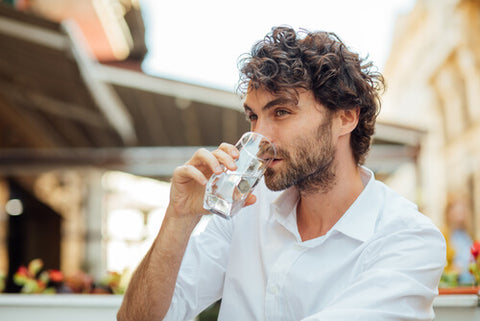 Man In A White Shirt Taking A Sip Of Water
