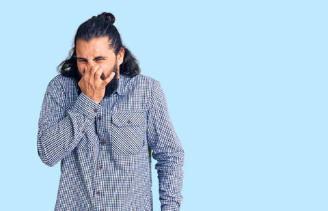 Man With Long Hair And Button Down Holding His Nose