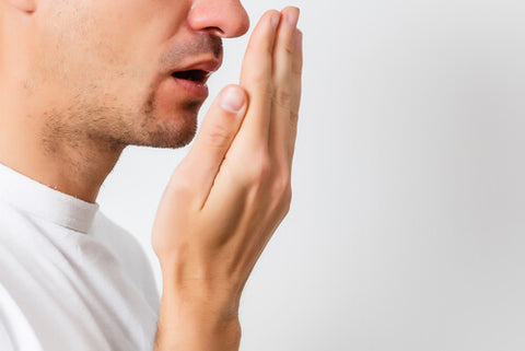 Man Smelling His Breath By Blowing Into His Hand