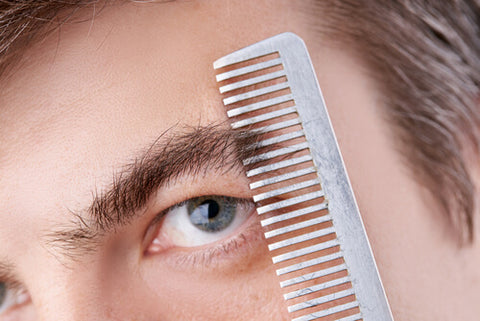Man Using A Comb To Trim His Eyebrows