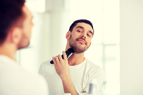 Man Trimming His Beard With A Body Groomer