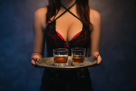 Woman Carrying Two Glasses Of Whiskey