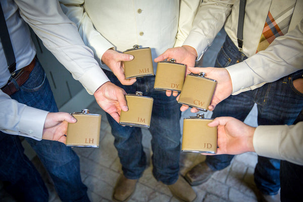 groomsmen with personalized flasks