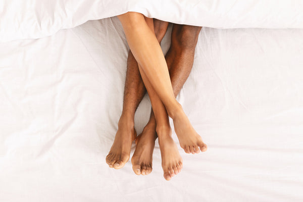couple's legs in bed