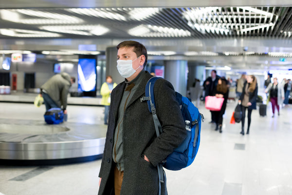man waiting for baggage with a mask on