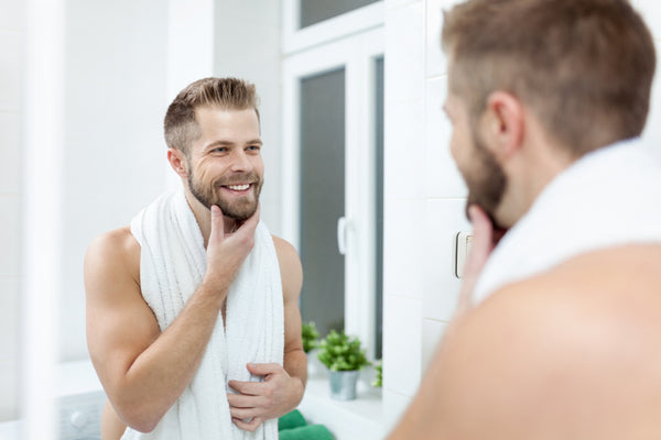 Man Grooming His Beard In The Mirror