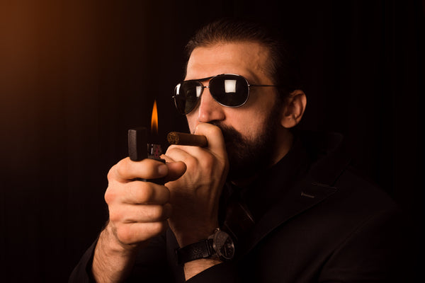 man lighting cigar
