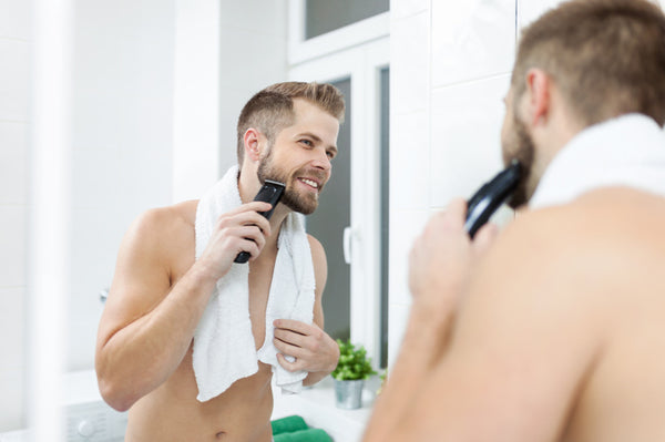 man shaving with trimmer in a mirror