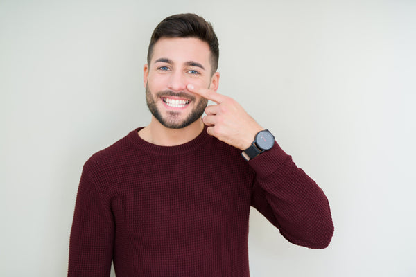 man pointing at nose hair