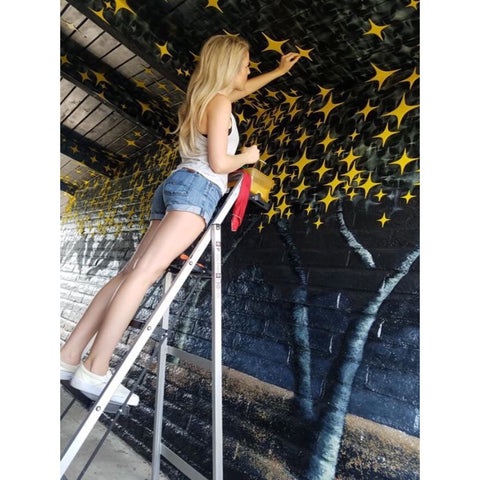 Christina Thomas the artist placing plexiglass stars on her mural at Hotel McCoy in Tucson Arizona