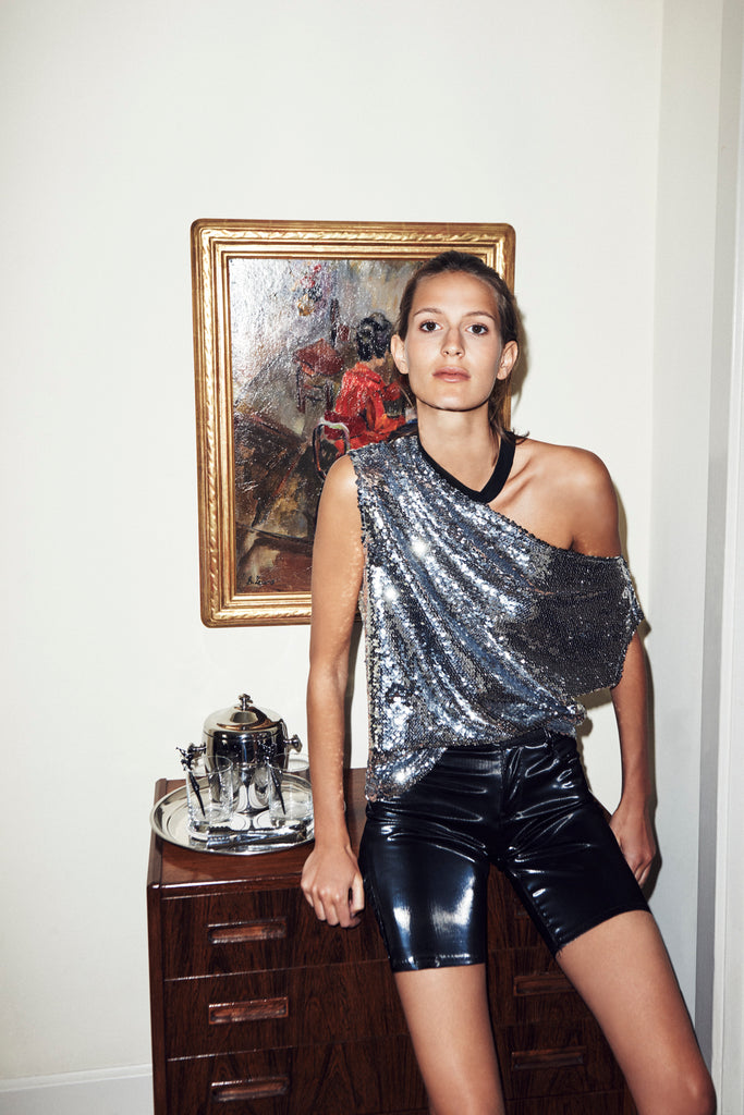 Female modeling silver sequins tee paired with leather shorts