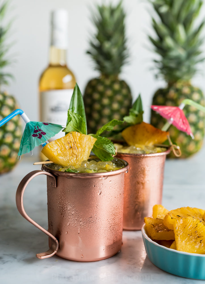 two copper mugs filled with ice and pineapple and mint leaves wedged on the rim