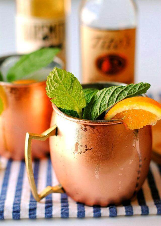 two copper mugs filled with ice orange slice wedged on the rim