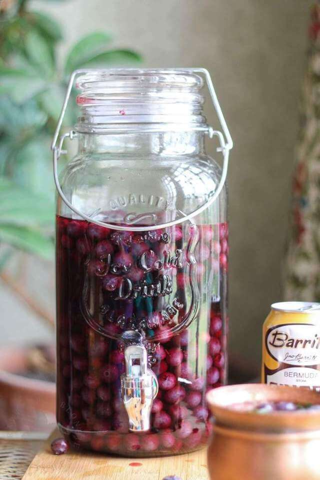 clear mason jug containing with dark pink liquid and blueberries