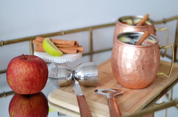 two Moscow Muled copper mugs filled with liquid apple slices and cinnamon sticks