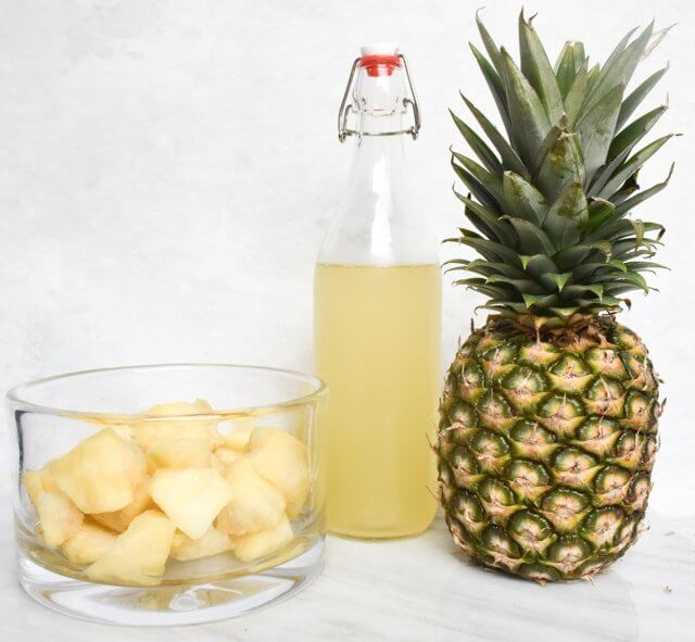 pineapple cubes placed in a clear glass jar beside a bottle and pineapple