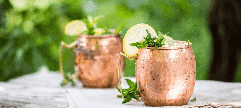 two Moscow Muled mugs filled with drink, mint leaves and slice of lemon