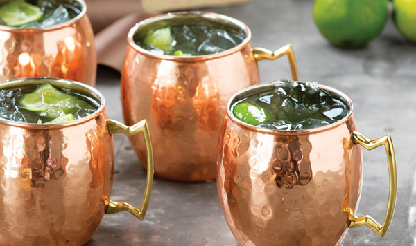 Moscow Muled copper mugs filled with clear liquid ice cubs and lime slices