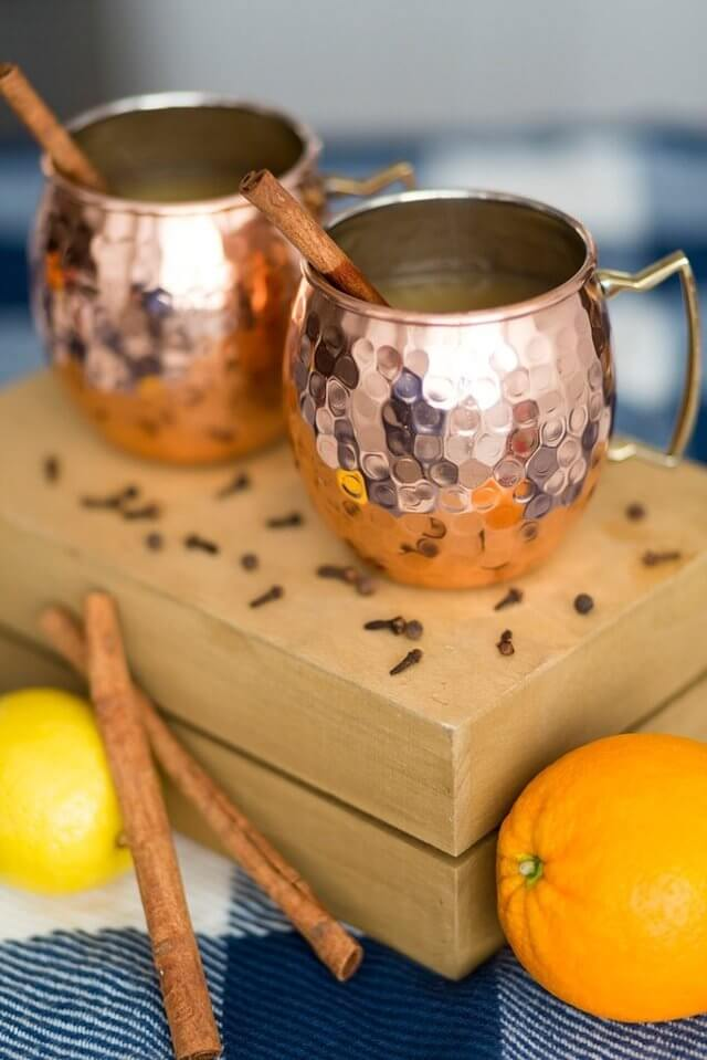 two Moscow Muled copper mug with cinnamon sticks sticking out placed on a wooden board