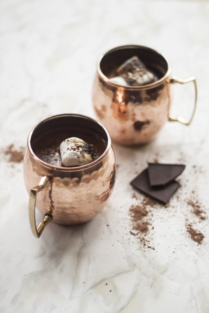 two Moscow Muled copper mugs filled with chocolate drink and marshmallows