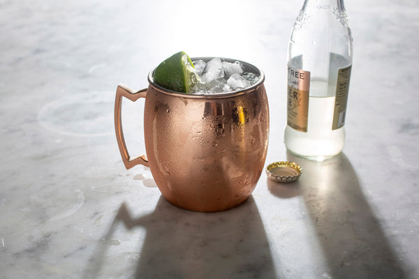 copper mug filled with liquid ice and lime beside a bottle