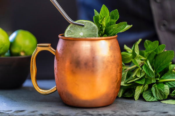copper mug side view with slice lime and mint leaves