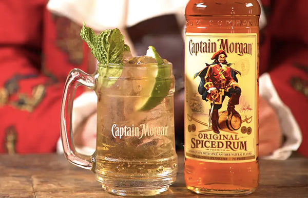 clear mug filled with liquid ice mint leaves and lime slices beside Captain Morgan Original Spiced Rum bottle
