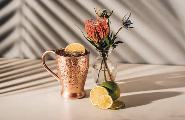 decorative copper mug filled with liquid ice and citrus slice beside a clear glass vase with flowers