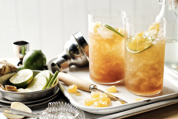 two clear glass filled with yellow liquid ice and citrus slices