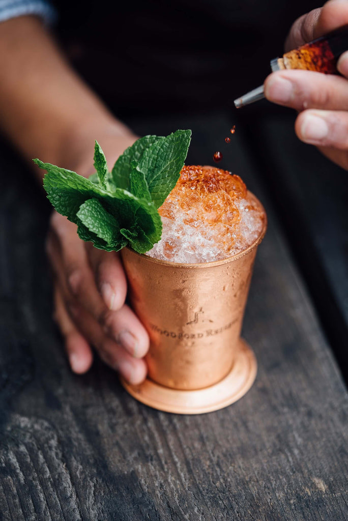 hand holding copper cup filled with crushed ice and mint leaves