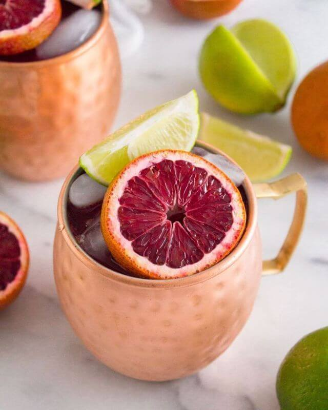 Moscow Muled copper mug filled with liquid ice pomegranate and lime slices