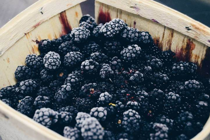 wooden box filled with blackberries close up view