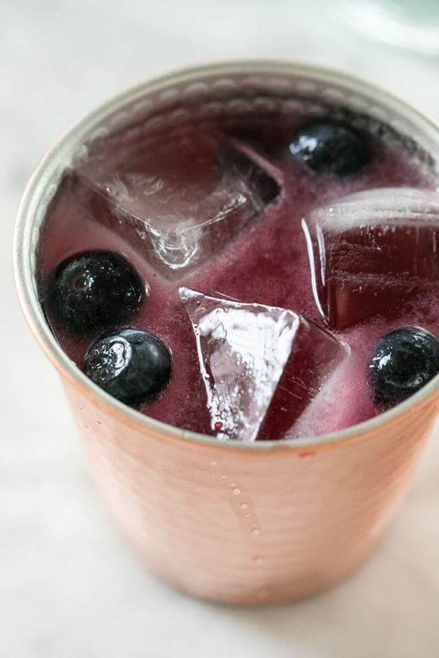 copper cup filled with purple liquid blueberries and ice cubes