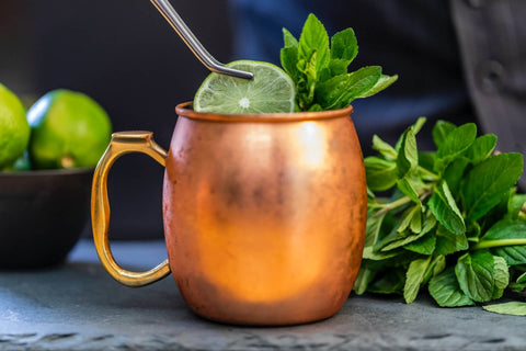 side view of copper mug with slice of lime and mint leaves