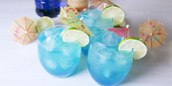 three clear glass filled with blue liquid ice cubes and sliced lime and umbrella wedged on the rim