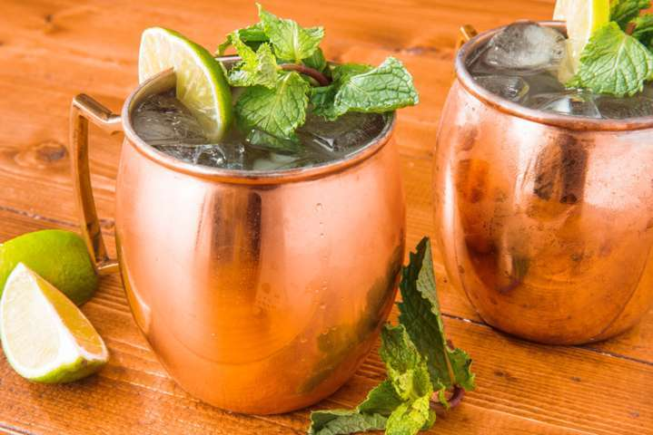 two copper mugs filled with liquid ice and mint leaves placed on a wooden surface