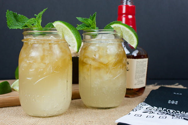 two clear Mason jar glass filled with yellow beverage ice mint leaves and citrus slice