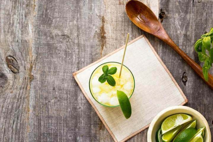 glass filled with yellow liquid beside wooden spoon placed on a wooden surface