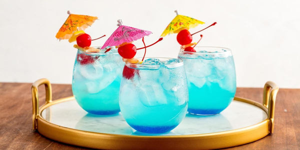three clear glasses filled with blue liquid ice cubes and tiny umbrella