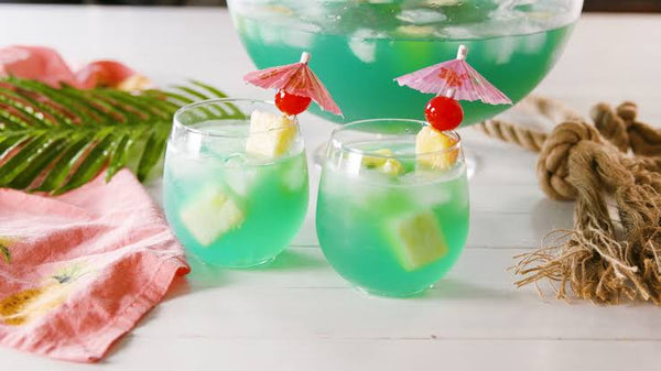 two clear glass filled with bluish green liquid with pineapple skewers and tiny umbrellas