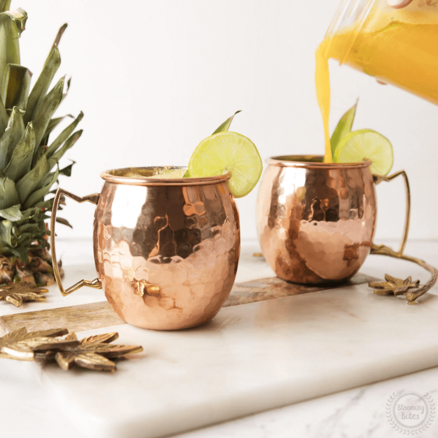 two Moscow Muled copper mugs with citrus slice on its rim and hand pouring yellow liquid into one mug